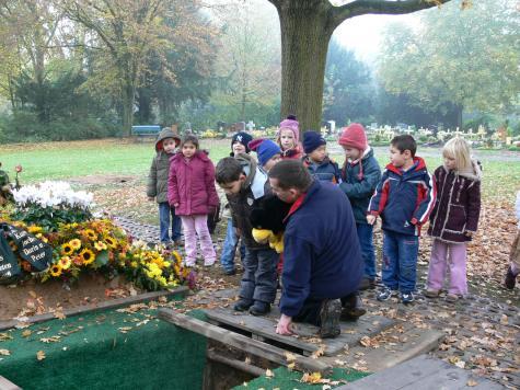 Eine neue Grabstelle wird betrachtet. Unter Anleitung von Friedhofsleiter Herbert Schimmel überlegen die Kinder wie eine Beerdigung abläuft. (Foto: Treuhandstelle)